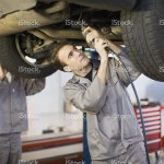 stock-photo-78492471-mechanic-working-on-car-engine-in-garage